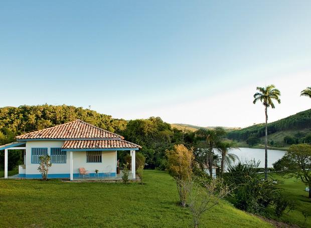 """Pintada de branco e azul hortênsia, a fachada é comum nas casas desta fazenda, assim como a paliçada – grade de madeira, característica da arquitetura bandeirista – nas janelas e a varanda em """"L"""" com vista para o grande lago (Foto: Edu Castello)"""