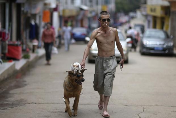 Xu Jin protagonizou cena épica ao andar com o cão, que também estava de óculos escuros, e levava o gato de estimação na cabeça (Foto: Wong Campion/Reuters)
