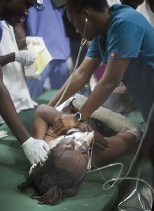 Mulher ferida durante acidente em celebração do carnaval no Haiti é tratada em hospital nesta terça-feira (17) em Porto Príncipe (Foto: Dieu Nalio Chery/AP)
