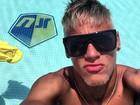 De barba e cabelos loiros, Neymar curte piscina com seu nome no fundo