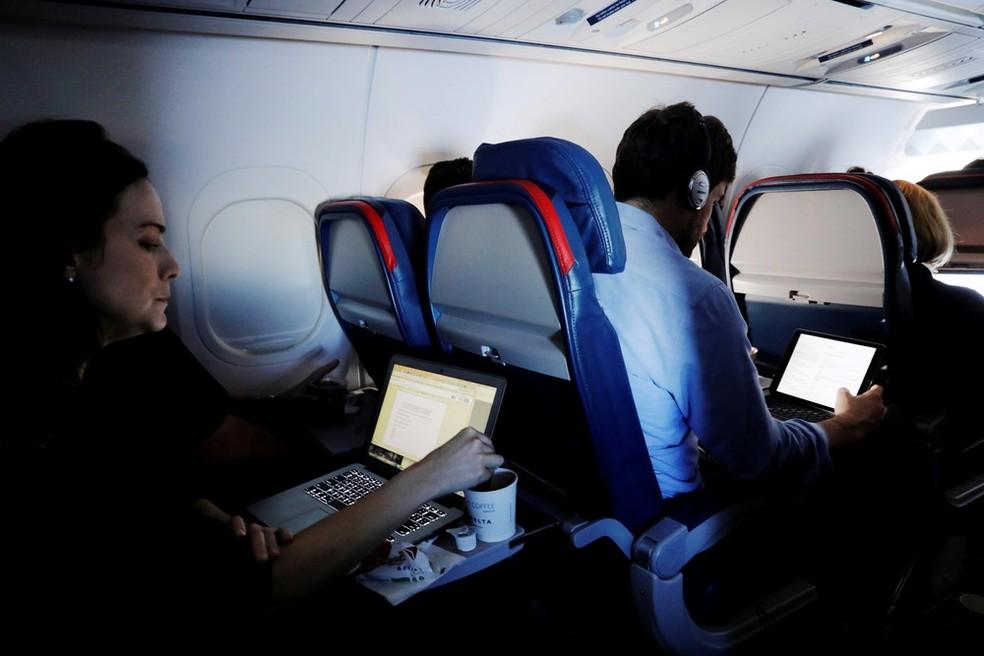 Passageiros usam computadores durante voo nos EUA (Foto: Lucas Jackson/Reuters)