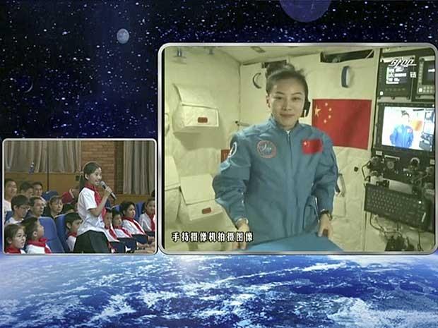 Jovem aluna faz pergunta através de videoconferência para a astronauta e professora Wang Yaping. (Foto: CCTV / AP Photo)