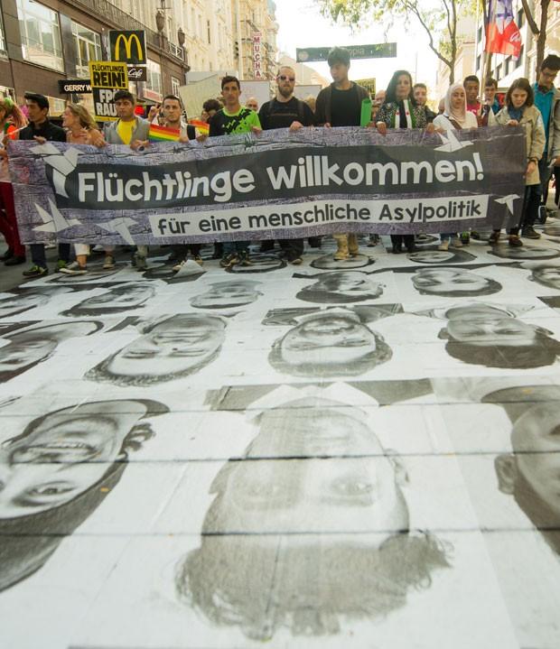 """Os participantes estavam com faixas nas quais era possível ler """"Nenhum ser humano é ilegal"""" e """"Refugiados são bem vindos, para uma política de asilo humana"""" (Foto: Christian Bruna/AP)"""