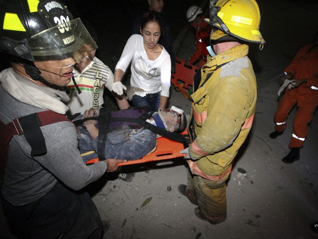 Vitima é regastada após desabamento de luxuoso edifício residencial na noite deste sábado (12), na cidade de Medellín (Foto: AFP)