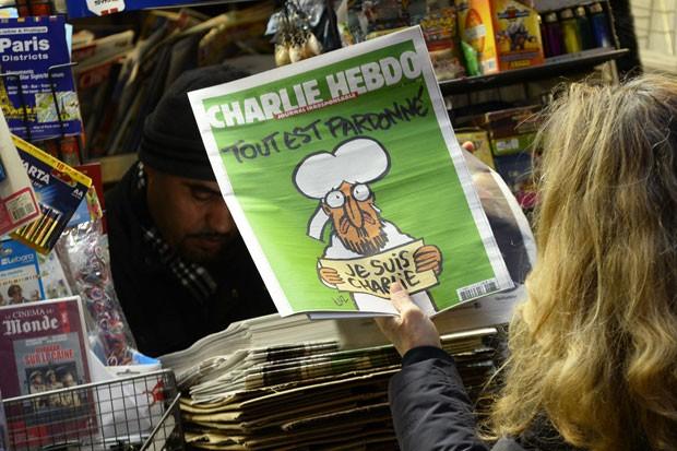 Mulher segura a nova edição do jornal 'Charlie Hebdo', com Maomé na capa, em banca de jornal em Paris nesta quarta-feira (14) (Foto: Bertrand Guay/AFP)
