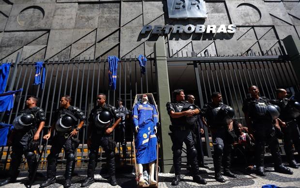 Policiais protegem a entrada do prédio da Petrobras ao lado de boneco com uniforme dos trabalhadores dentro de um caixão simbólico (Foto: Ricardo Moraes/Reuters)