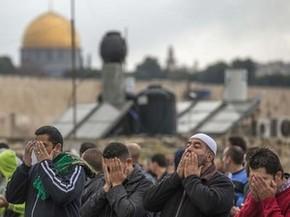 Palestinos muçulmanos rezam nesta sexta-feira em bairro no leste de Jerusalém, com a Esplanada das Mesquitas ao fundo (Foto: AFP PHOTO / JACK GUEZ)