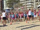 Crianças e adultos praticam atividades físicas em praia do ES