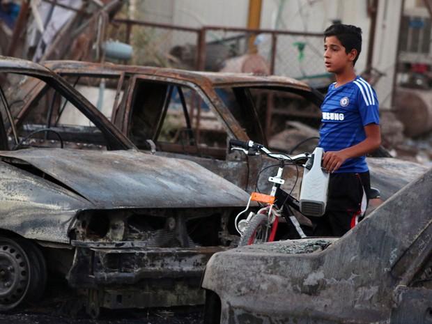 Garoto passa por local destruído após ataque em mercado de carros próximo a Sadr City, no Iraque (Foto: AFP/Haidar Mohammed Ali)
