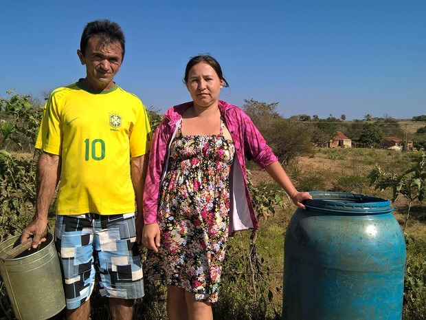 Sem o benefício do poço, Márcia Michele e Ivanildo Honorato dependem da água de um barreiro para ajudar a lavar as coisas em casa (Foto: Diogo Almeida/G1)