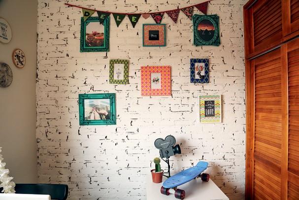 No escritório o outro lado da parede de tijolinhos ganhou pintura branca e quadrinhos (Foto: Victor Affaro)