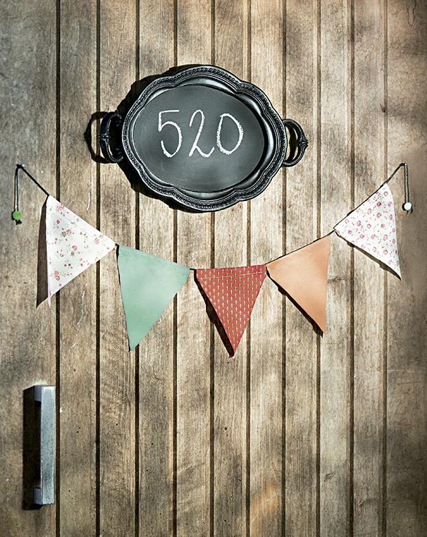 Boas-vindas diferentes: bandeirinhas Botões de Amora na porta e o número da casa escrito na bandeja-lousa Corporação de Ofícios (Foto: Cacá Bratke/Editora Globo)