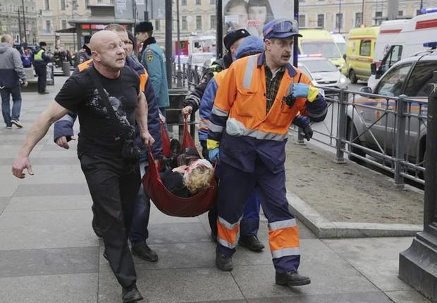 Bombeiros e equipe de resgate transportam mulher ferida em atentado no metrô de São Petersburgo, na Rússia (Foto: Anton Vaganov/EFE)