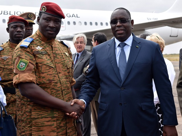 O tenente-coronel Isaac Zida cumprimenta o presidente senegalês Macky Sall durante sua chegada ao aeroporto de Ouagadougou, na quarta (5) (Foto: AFP Photo/Issouf Sanogo)