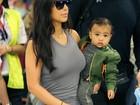 Kim Kardashian viaja com a filha descalça no colo