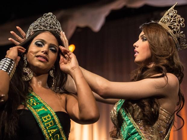 A vencedora, Raika Ferraz (esq.), é coroada por sua antecessora como a Miss T Brasil 2013 (Foto: Yasuyoshi Chiba/AFP)