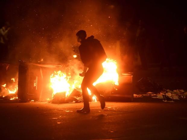 Manifestante passa diante de barricada de lixo em chamas durante protesto em Oakland, Califórnia, após a eleição de Donald Trump como novo presidente dos EUA (Foto: Noah Berger/Reuters)