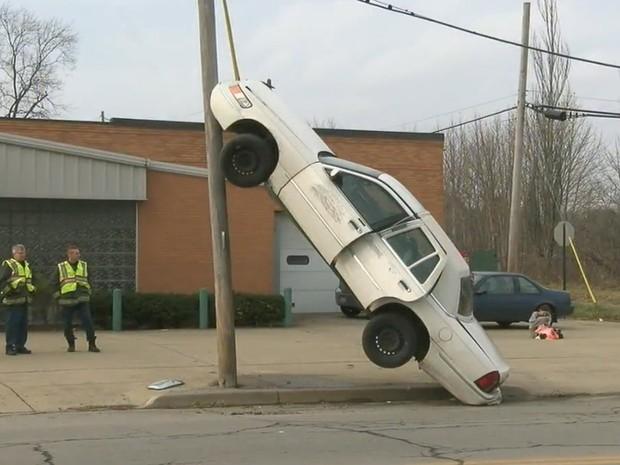 Mulher se distraiu e ficou com carro na vertical ao atingir poste nos EUA (Foto: Reprodução/YouTube/WKBN27)