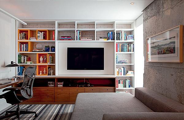 Sala de TV/ escritório | Maicon Antoniolli desenhou tanto o sofá, que serve de cama, quanto a estante com nichos, além da mesa  de trabalho. A cadeira Aeron, da Herman Miller, é encontrada na Atec. Tapete da By Kamy (Foto: Marco Antonio)