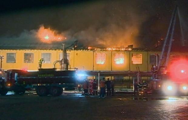 Bombeiros tentam impedir que as chamas cheguem a sede de empresa de transportes (Foto: Reprodução/RBS TV)