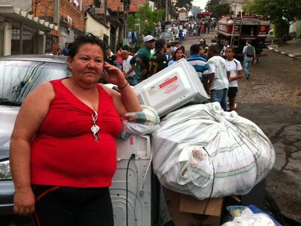 Sebastiana cuida dos objetos retirados da casa da filha: é a terceira vez que o fogo afeta moradia da família (Foto: Paulo Toledo Piza/G1)