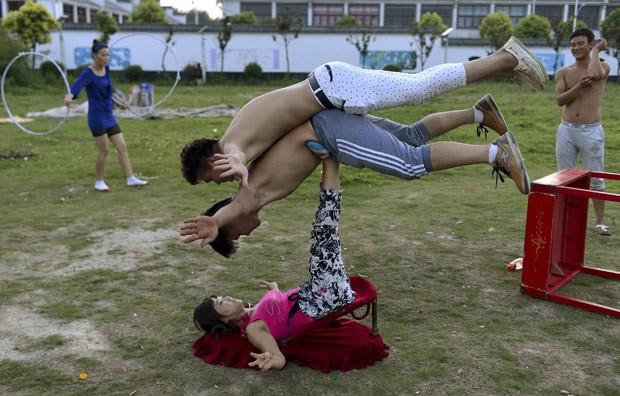 Chinesa mostrou força e técnica ao suspender dois homens com as pernas (Foto: Reuters)