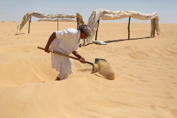 Funcionário cava buraco para enterrar paciente na areia do oásis de Siwa (Foto:  Reuters/Asmaa Waguih)