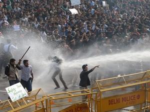 Milhares de pessoas protestaram neste sábado (22) em Nova Délhi, na Índia, contra o estupro de uma estudante de 23 anos de idade em um ônibus. Os manifestantes tentaram marchar em direção do palácio presidencial, mas a polícia impediu. (Foto: Raveendran/AFP)