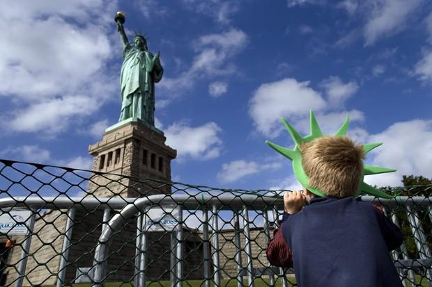 Jackson Blendowski, de 6 anos, observa a Estátua da Liberdade durante a reabertura ao público nos EUA (Foto: John Minchillo/AP)