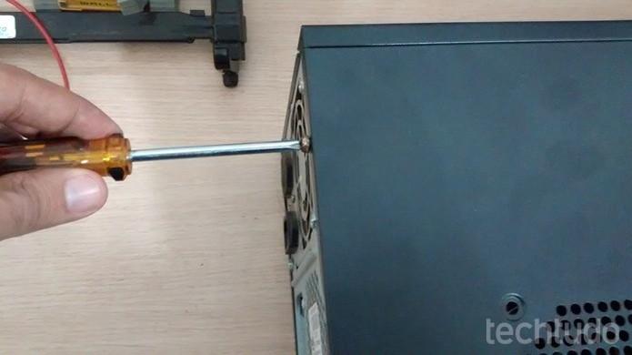 Desconecte seu computador da energia e coloque-o deitado sobre uma mesa (Foto: Dario Coutinho/TechTudo)