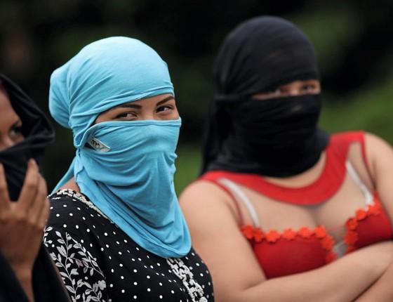 Mulheres á espera de notícias usam máscaras para não serem identificadas  (Foto:  Ueslei Marcelino / Reuters)