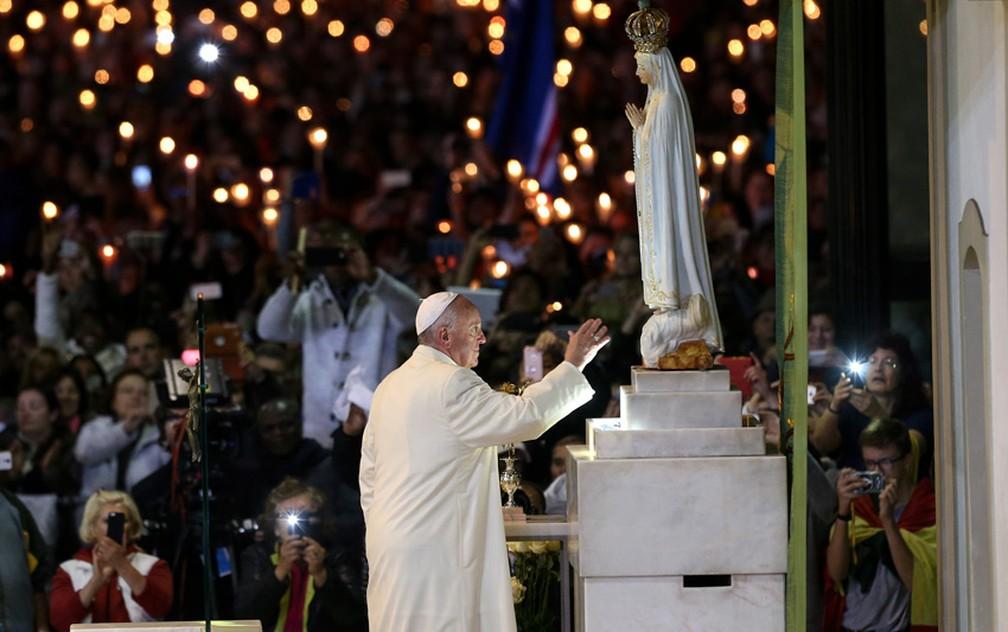Papa Francisco toca a imagem de Nossa Senhora de Fátima durante cerimônia no santuário português, nesta sexta-feira (12) (Foto: Jose Sena Goulao/Reuters)