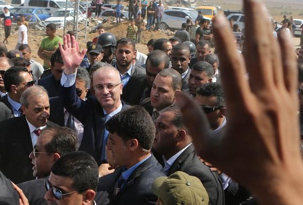 O primeiro-ministro palestino, Rami Hamdallahm, cumprimenta morador ao visitar área de Gaza destruída por conflito com Israel nesta quinta-feira (8), em visita ao território para reunião do governo de unidade (Foto: Said Khatib/AFP)