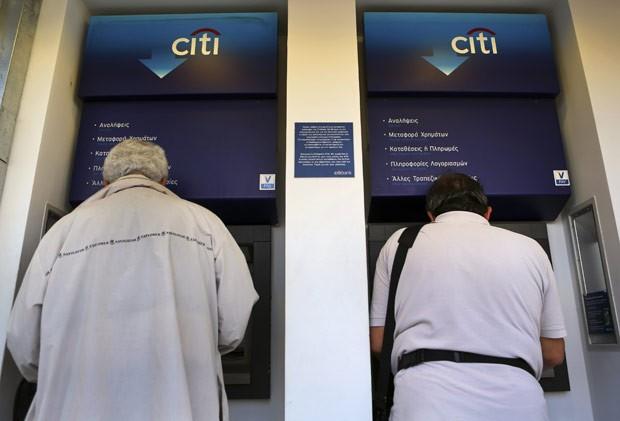 Gregos retiram dinheiro de caixa eletrônico nesta quarta-feira (16) em Atenas (Foto: Reuters)