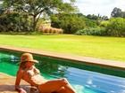 Carol  Magalhães exibe barriga sarada na beira da piscina
