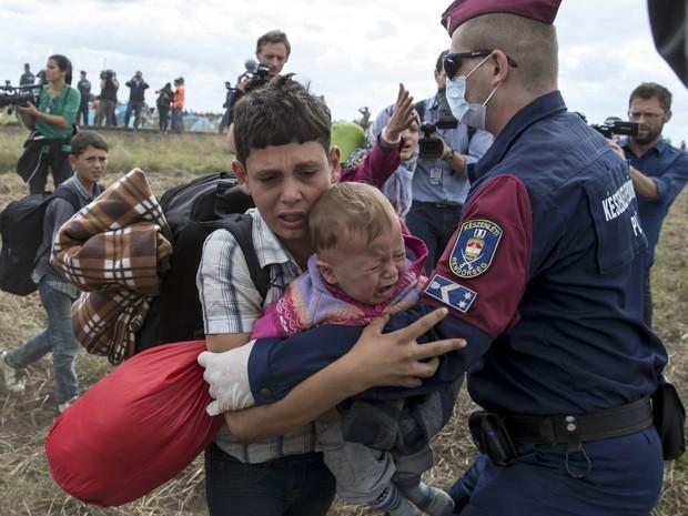 Policial húngaro tenta deter um menino migrante que carrega um bebê chorando em seu colo enquanto tentam passar por um ponto de controle na vila de Roszke, na Hungria (Foto: Marko Djurica/Reuters)