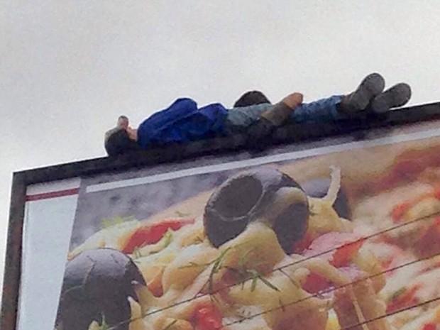 Homem ficou desacordado em cima de outdoor após sofrer choque (Foto: Tarcísio Júnior)