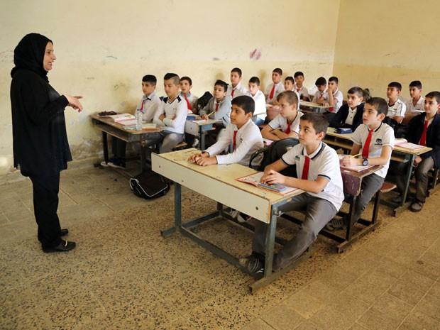 Alunos têm aula com professora em escola (Foto: Ahmed Saad/Reuters)