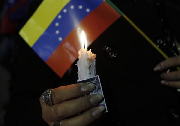 Mulher participa de vigília pela saúde de Chávez na noite desta segunda-feira (10) em La Paz, na Bolívia (Foto: AFP)