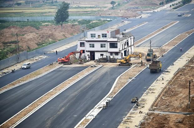 Prédio foi deixado no meio de estrada récem-construída na China (Foto: Reuters)
