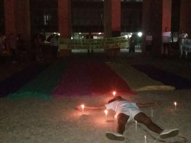 Manifestante deitado sobre bandeira LGBT (Foto: Divulgação/Mariana Requiri)
