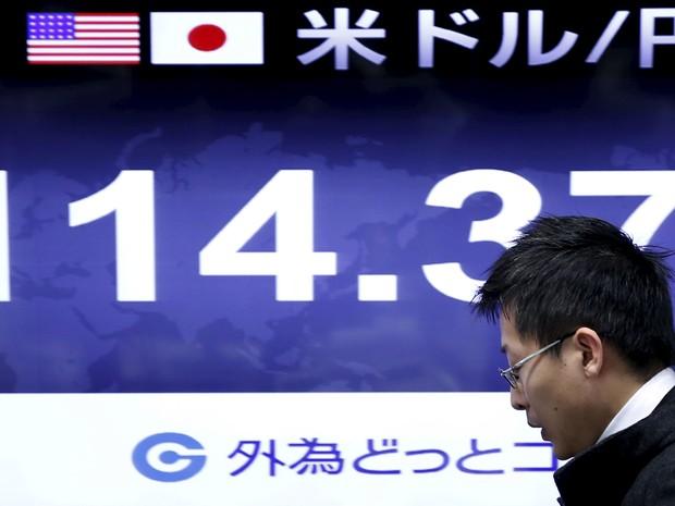 Funcionário de uma casa de câmbio passa em frente a painel com a cotação do iene frente ao dólar nesta terça-feira. (Foto: Reuters)