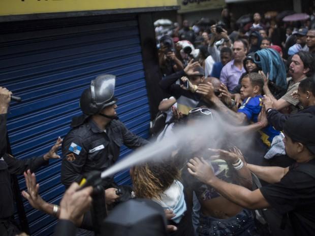 Policial usa spray de gás lacrimogêneo contra multidão durante protesto de moradores da favela Pavão-Pavãozinho no dia do enterro do dançarino Douglas Rafael da Silva Pereira (Foto: Felipe Dana/AP)
