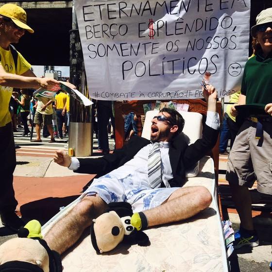 """Manifestante deita em berço """"e$plendido"""", em crítica a políticos corruptos (Foto: Luís Lima/ÉPOCA )"""