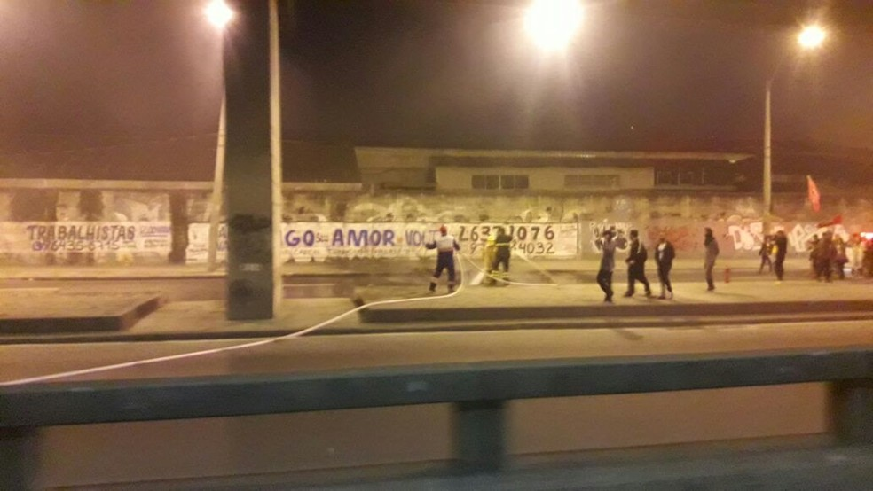Equipes  da concessionaria que administra a Ponte Rio-Niterói apagam fogo para liberar a via após protesto (Foto: Miguel Folco/ G1)