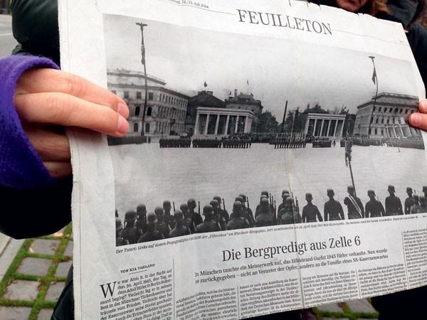 Muitas memórias: A guia da excursão, Tina Olschlager, mostra um jornal antigo com foto de praça onde o exército de Adolf Hitler fazia demonstrações de poder. O passeio a pé que conta a história do nazismo na cidade é o mais procurado entre os turistas (Foto: Magrit Behrens, Zentralinstitut Kunstgeschichte)