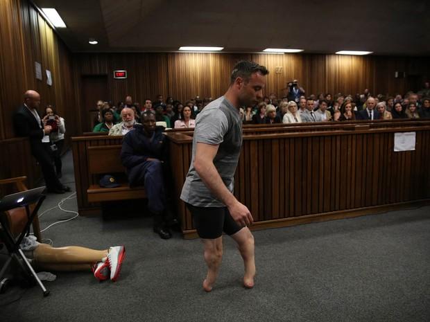 O medalhista paralímpico Oscar Pistorius caminha sem suas próteses de pernas na corte durante nova audiência na Alta Corte em Pretória, África do Sul. Ele aguarda para ouvir a nova sentença no caso de homicídio de sua namorada, Reeva Steenkamp, em 2013 (Foto: Siphiwa Sibeko/AFP)