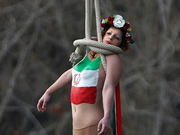 Uma ativista do grupo de direitos das mulheres FEMEN se pendura em uma ponte durante um protesto contra Hassan Rohani, presidente do Irã, que visita Paris, na França (Foto: Charles Platiau/Reuters)