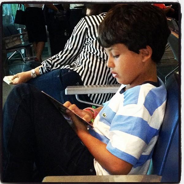 Miguel, 9, concentrado na leitura enquanto aguarda o avião (Foto: Reprodução/Instagram)