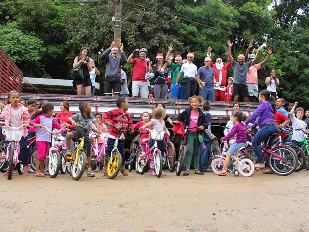 Crianças e voluntários posam em frente ao caminhão que levou as bikes  (Foto: Rafael Stedile/Divulgação)